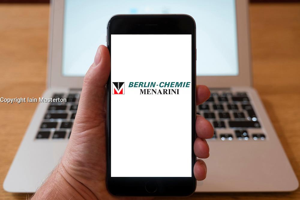 Using iPhone smartphone to display logo of Berlin-Chemie  Menarini, an international research-based pharmaceutical company