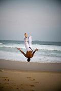 A Capoeirista performs a backflip during his Capoeira practice on Leblon beach in Rio de Janeiro, Brazil