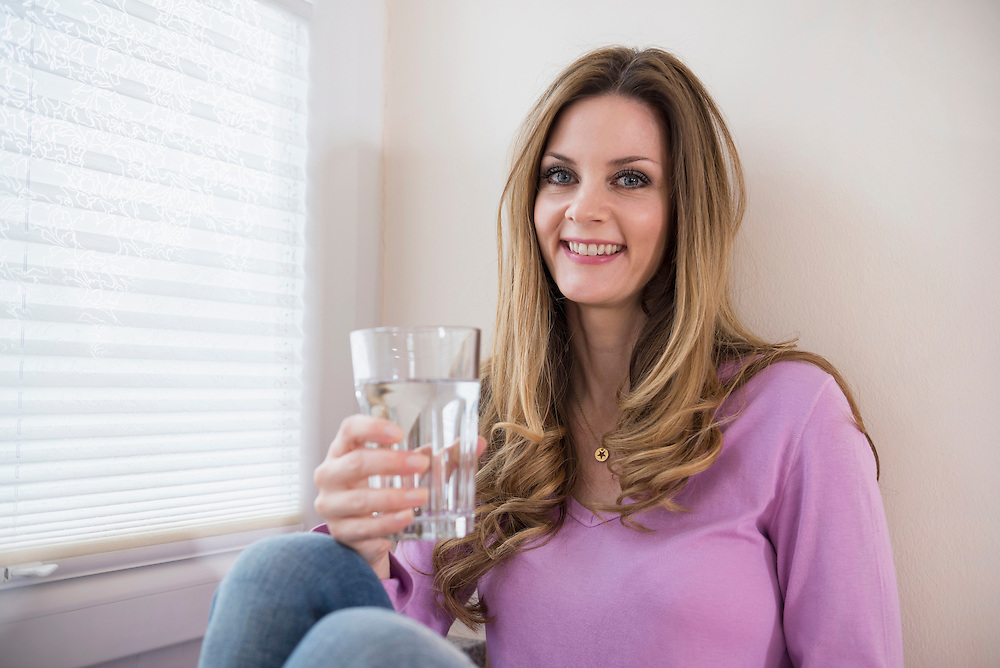 Smiling mature woman holding glass at the window