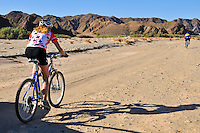 Biking through Wadi Gemal National Park with the Red Sea Mountains in the background.