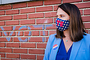 13 OCTOBER 2020 - DES MOINES, IOWA: THERESA GREENFIELD, the Democratic candidate for the US Senate in Iowa, talks to reporters in front of brick wall at the Polk County Auditor's Office. Greenfield, the Democratic candidate for US Senate, dropped off her completed ballot at the Polk County Auditor's Office in Des Moines. Greenfield is running against incumbent US Senator Joni Ernst, a Republican. Greenfields holds a slight lead over Ernst in recent polling.       PHOTO BY JACK KURTZ