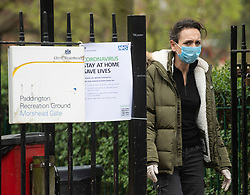 © Licensed to London News Pictures. 28/03/2020. London, UK. A woman wearing a medical face mask walks past an NHS sign asking people to stay at home, at Paddington Recreation Ground in London, during a lockdown over the spread of COVID-19. Prime Minister Boris Johnson has announced that people should only leave their homes for essential work, groceries, medical necessity and exercise. Photo credit: Ben Cawthra/LNP