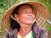 08 APRIL 2010 - NAKHON PHANOM, THAILAND: A Thai rice farmer near her paddy in Nakhon Phanom province, Thailand. She said this year's rice crop was not as good as last year and that there was less rain than last year. But she said it was more troubling that some rain fell when it is normally dry and very little rain fell during the rainy season. She said she is very concerned about her livestock, which graze off the rice stalks. She said with so little rice that were few rice stalks and she is concerned her ox and buffalo could die. The region is in the midst of a record setting drought and the Mekong River is at its lowest point in nearly 50 years, setting up an environmental disaster the region has never seen before. Many of the people who live along the river farm and fish. They claim their crops yields are greatly reduced and that many days they return from fishing with empty nets. The river is so shallow now that fisherman who used to go out in boats now work from the banks and sandbars on foot or wade into the river. In addition to low river levels the Isan region of Thailand is also in the midst of a record drought and heat wave. Farmers have been encouraged to switch from rice to less water intensive crops and to expect lower yields. Farmers here rely more on rain fall than irrigation to water their crops.       PHOTO BY JACK KURTZ