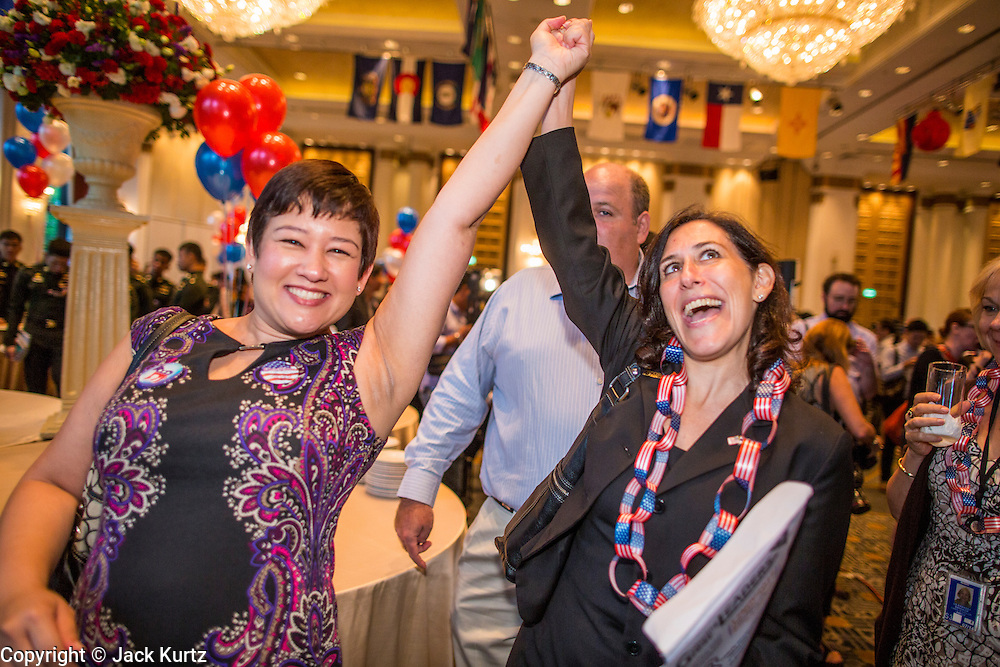 07 NOVEMBER 2012 - BANGKOK, THAILAND:  KATHERINE APHAIVONGS, left, and KAREN HOCHHAUSER celebrate US President Barrack Obama's apparent reelction at the US Embassy's election watch party in Bangkok. They both supported President Obama's reelection. US President Barack Obama won a second term Tuesday when he defeated Republican Mitt Romney. Preliminary tallies gave the President more than 300 electoral votes, well over the 270 needed to win. The election in the United States was closely watched in Thailand, which historically has very close ties with the United States. The American Embassy in Bangkok sponsored an election watching event which drew thousands to a downtown Bangkok hotel. American Democrats in Bangkok had their own election watch party at a restaurant in Bangkok.           PHOTO BY JACK KURTZ