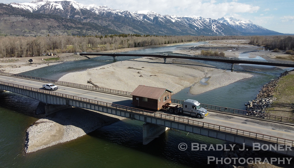 Vern Woulstenhume of Teton Transport hauls a 22x22-foot house across the Snake River on Friday morning. When the owners decided to build a new residence on their property in Wilson they donated the existing house to a friend in Teton Valley, who paid for the moving costs. The house had to be hauled through Wilson, Alpine and Swan Valley to its destination in Victor due to size and weight restrictions on Teton Pass.