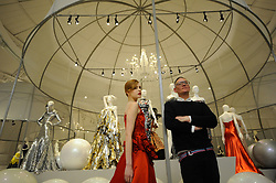 © Licensed to London News Pictures. 14/05/2012. London, UK. Model Zhanna Emelyanova poses in a red dress with designer Giles Deacon at a photocall for a Glorious ballgowns exhibition at the V&A's refurbished Fashion gallery in London on May 14, 2012. The show is exhibiting British Glamour Since 1950. Photo credit : Thomas Campean/LNP