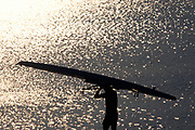 Silhouette of rower carrying his boat.