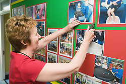 Teacher pinning photos of pupils onto a notice board in the school corridor,