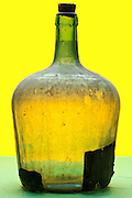 empty with dust covered old glass wine container object on yellow green background