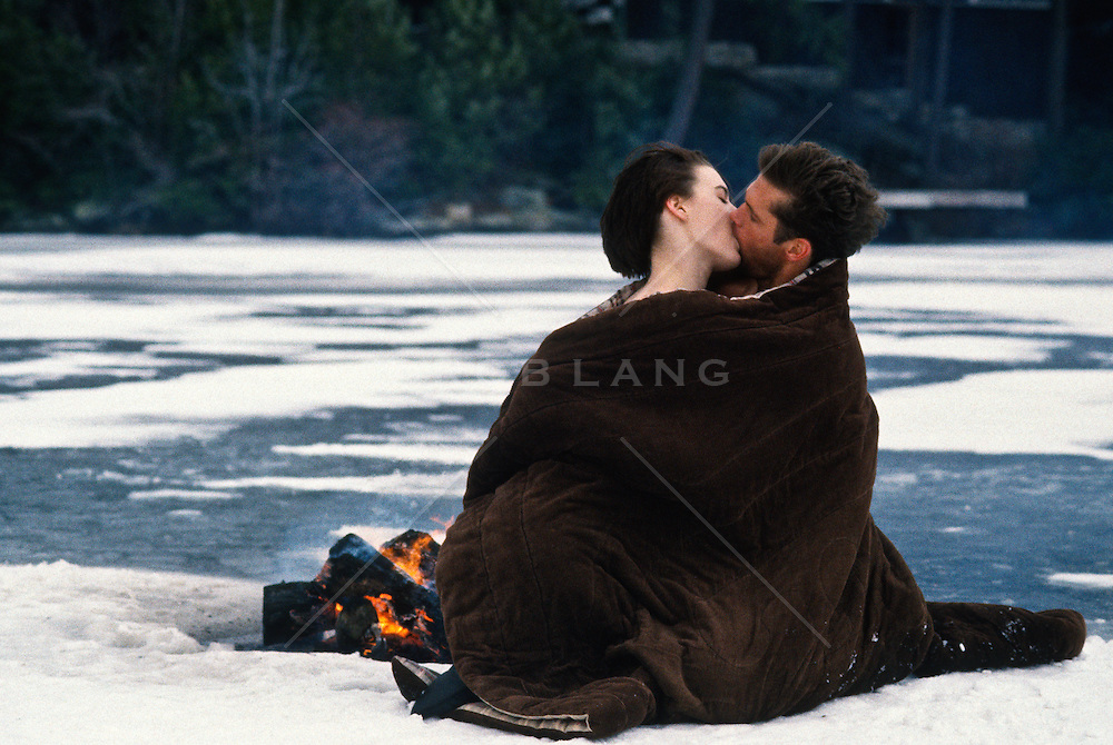 couple kissing and wrapped in a blanket  by a fire on a frozen lake