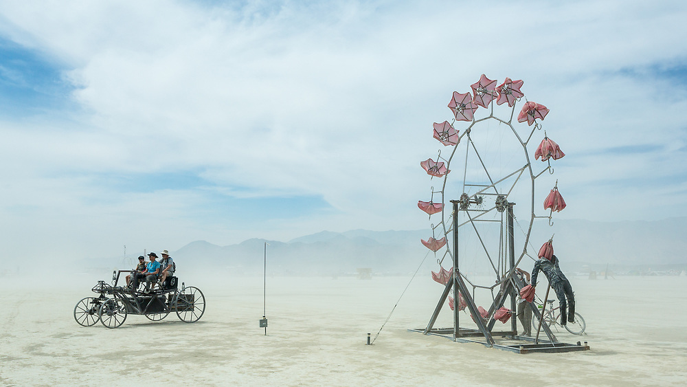 Mutant Vehicle and Parasolvent by: Dan Benedict from: Anaheim, CA year: 2014<br /> <br /> Parasolvent is a mechanical expression of loss, release, healing and decay. Participants turn a crank to rotate a 20' tall ring of red parasols. The collapsed parasols rise up through the chest cavity of a human figure and gradually open as they climb upwards, reaching full extension at the apex, and slowly closing as they descend.<br /> This piece is a meditation on the idea that engineering and architecture can create a space or object that acts a vessel for spiritual healing; imagining something we have held inside of us, be it sickness or pain, leaving us, rising, blossoming and decaying.<br /> <br /> Contact: dan@benedictaugust.com