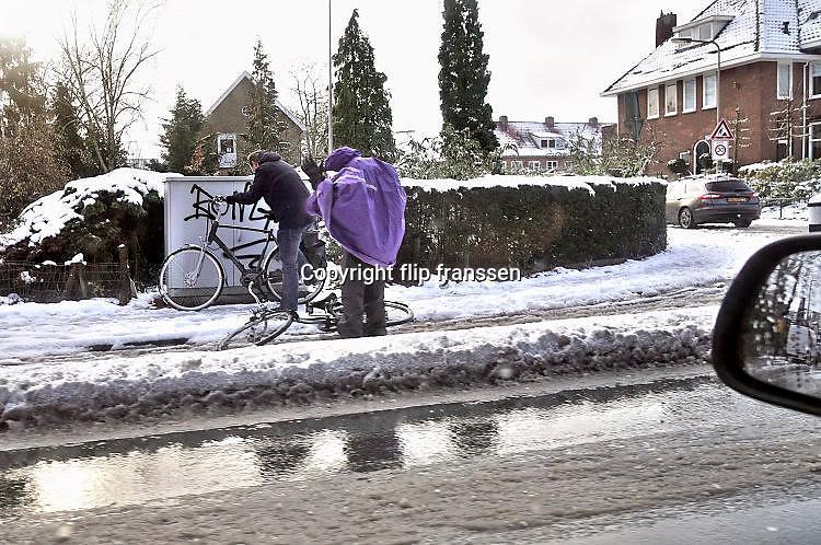 Nederland, Oosterbeek, 9-12-2017In de omgeving van Arnhem is in de nacht veel sneeuw gevallen. De eerste van deze winter. Deze fietser is uitgegeleden op het fietspad en krijgt hulp van een voorbijganger. Het verkeer had er veel last van, en sneeuwschuiver en strooiwagen worden ingezet om de wgen begaanbaar te houden.Foto: Flip Franssen