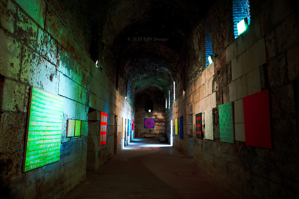 Unknown contemporary abstract and geometric paintings illuminated by sunlight streaming from upper arched openings that give light to the underground structure.
