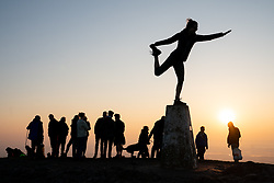 © Licensed to London News Pictures. 21/04/2019. Worcester, UK. A woman performs a yoga pose after a religious service at sunrise on Easter Sunday, at the Worcestershire Beacon. The Beacon is the highest point in the Malvern Hills at 425m. Easter Sunday is a key date in the Christian calendar. Photo credit : Tom Nicholson/LNP