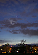 Middletown, New York - The crescent moon, partly hidden behind clouds, and Venus, to the upper right of the moon, shine in the western sky after sunset on April 24, 2012.