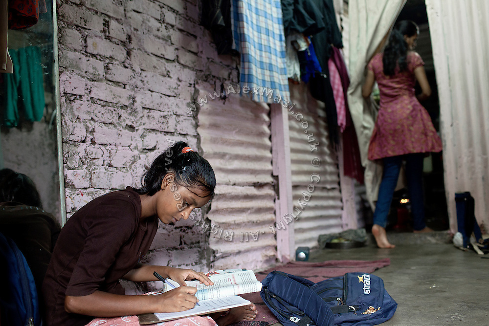 Mayuri Mahesh Pandit, 13, (left) is completing her school homework before leaving to participate at the Unicef-run 'Deepshikha Prerika' project inside the Milind Nagar Pipeline Area, an urban slum on the outskirts of Mumbai, Maharashtra, India, where she resides with her family.