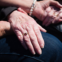Liverpool, UK, 25th May, 2013. A woman holds the hands of an ex-Royal Navy nurse during the service to honour those who died as part of the 70th anniversary celebrations of the Battle of the Atlantic.