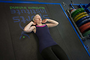 Partially-sighted skiing paralympian from the Sochi Olympics, Kelly Gallagher trains in the gym at the Sports Institute, University of Ulster, Northern Ireland, UK. Practicing sit-ups she starts a new training regime for the forthcoming winter season. Kelly Marie Gallagher, MBE is a Northern Irish skier and the first athlete from Northern Ireland to compete in the Winter Paralympics. Gallagher won Britain's first ever Winter Paralympic gold medal during Sochi 2014.