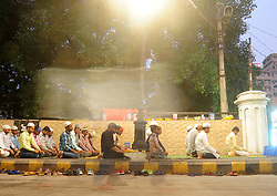 June 16, 2017 - Allahabad, Uttar Pradesh, India - Allahabad: Indian muslim offer prayer/Namaz after break their fast with iftar during the holy month of Ramadan at footpath in Allahabad on june 16,2017. Muslim men and women across the world observe Ramadan, a month long celebration of self-purification and restraint. During Ramadan, the Muslim community fast, abstaining from food, drink, smoking and sex between sunrise and sunset, breaking their fast with an Iftar meal after sunset. (Credit Image: © Prabhat Kumar Verma via ZUMA Wire)