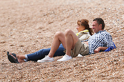 © Licensed to London News Pictures. 07/07/2014. Brighton, UK. A couple relaxing on Brighton Beach. South Coast recovers today with temperatures around 24C after a day with rain and clouds on Saturday. Photo Credit: Hugo Michiels/LNP