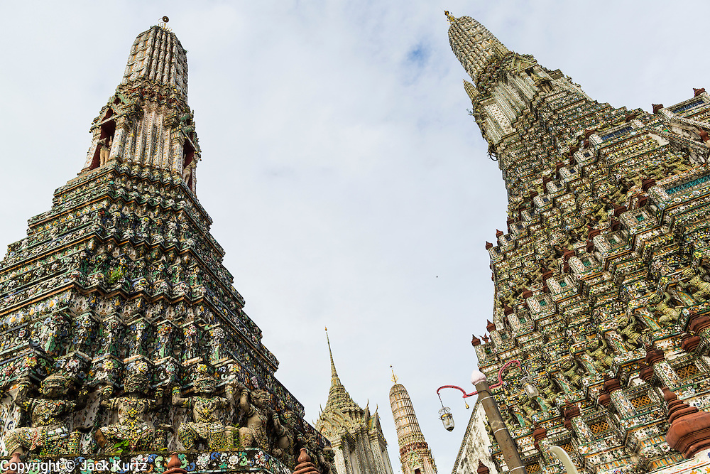 """23 SEPTEMBER 2013 - BANGKOK, THAILAND:  The central chedi at Wat Arun flanked by satellite chedis. The full name of the temple is Wat Arunratchawararam Ratchaworamahavihara. The outstanding feature of Wat Arun is its central prang (Khmer-style tower). The world-famous stupa, known locally as Phra Prang Wat Arun, will be closed for three years to undergo repairs and renovation along with other structures in the temple compound. This will be the biggest repair and renovation work on the stupa in the last 14 years. In the past, even while large-scale work was being done, the stupa used to remain open to tourists. It may be named """"Temple of the Dawn"""" because the first light of morning reflects off the surface of the temple with a pearly iridescence. The height is reported by different sources as between 66,80 meters and 86 meters. The corners are marked by 4 smaller satellite prangs. The temple was built in the days of Thailand's ancient capital of Ayutthaya and originally known as Wat Makok (The Olive Temple). King Rama IV gave the temple the present name Wat Arunratchawararam. Wat Arun officially ordained its first westerner, an American, in 2005. The central prang symbolizes Mount Meru of the Indian cosmology. The temple's distinctive silhouette is the logo of the Tourism Authority of Thailand.          PHOTO BY JACK KURTZ"""