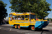 Tourists aboard a Duck Tour amphibious vehicle on Millbank in Westminter, London. There tours go on roads and on the River Thames.