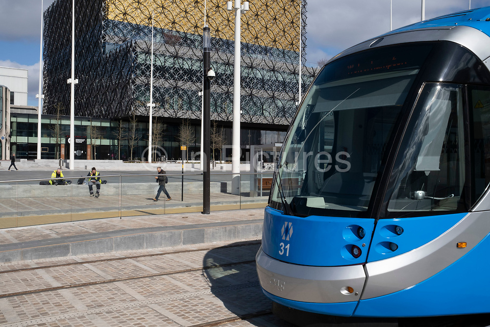 Public transport tram in Centenary Square and the Library of Birmingham in Birmingham city centre is virtually deserted due to the Coronavirus outbreak on 31st March 2020 in Birmingham, England, United Kingdom. Following government advice most people are staying at home leaving the streets quiet, empty and eerie. Coronavirus or Covid-19 is a new respiratory illness that has not previously been seen in humans. While much or Europe has been placed into lockdown, the UK government has announced more stringent rules as part of their long term strategy, and in particular social distancing.