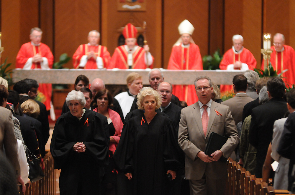 Illinois Supreme Court Justice Anne M. Burke (center) and Retired Chief Justice Mary Ann G. McMorrow (L) lead a procession of Members of the Catholic Lawyers Guild during the Annual Red Mass at Holy Name Cathedral, celebrated by Francis Cardinal George (background in red mitre).