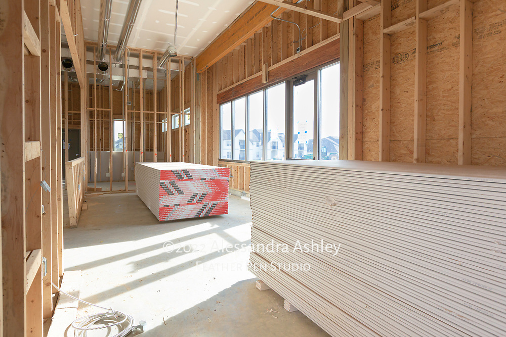 Drywall sheets are stacked and ready for installation at building site of new physical therapy and wellness center.