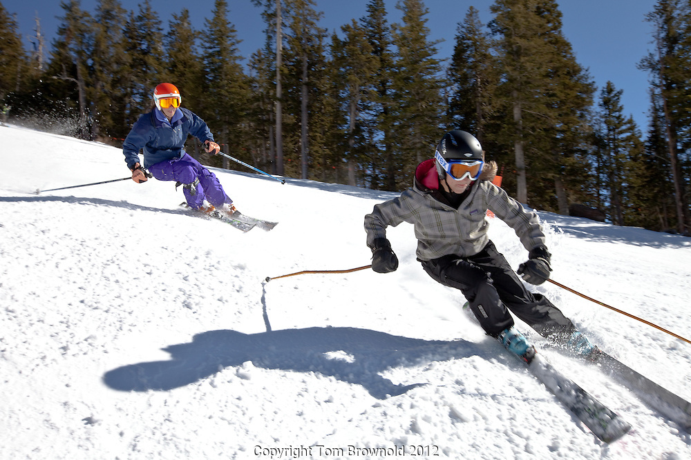 Women skiers skiing on a sunny hard packed surface day.