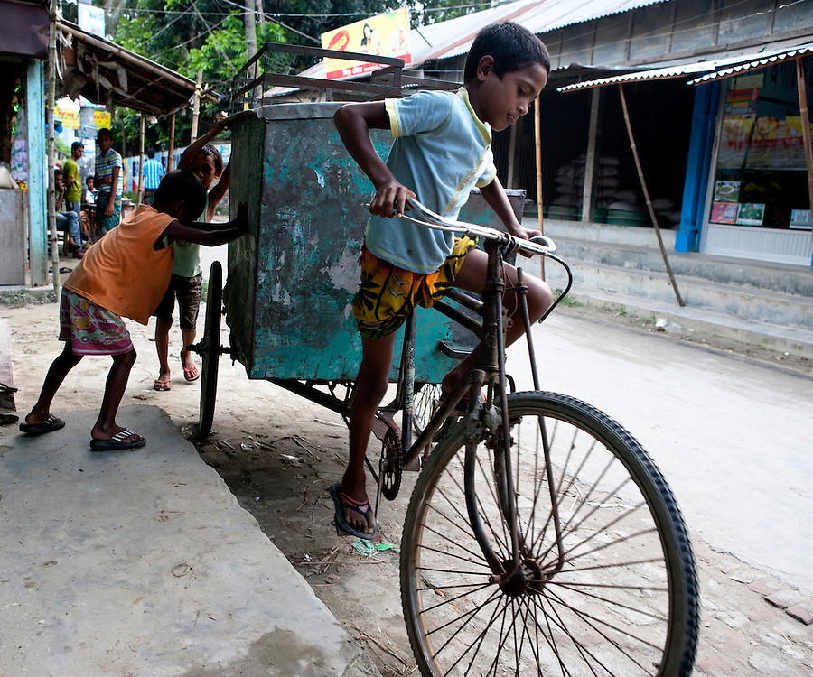 Children playing on the street with a rickshaw van