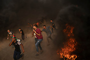 In this photo taken Friday, Aug. 31, 2018, Palestinian protesters run from teargas fired by Israeli troops during a protest at Gaza Strip's border with Israel, east of Gaza City. The 11-year blockade and growing anger have put a lot of pressure on Hamas, which is trying to redirect it toward Israel with relentless protests.