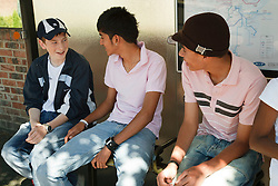 Group of teenage boys at bus stop.