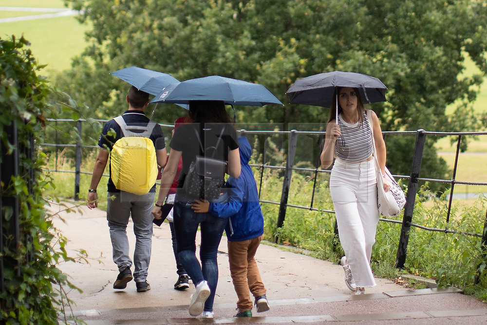 © Licensed to London News Pictures. 27/07/2021. London, UK. Members of the public use umbrellas to shelter from rain in Greenwich Park in South East London. A yellow weather warning for thunderstorms is in place for parts of England. Photo credit: George Cracknell Wright/LNP
