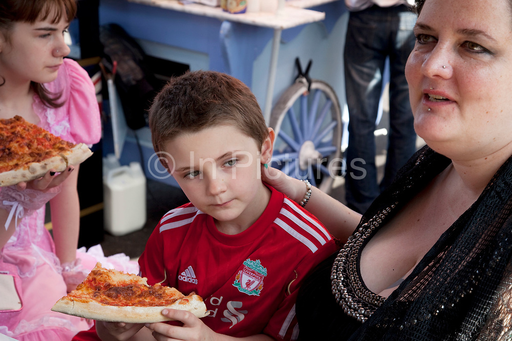 Mother Louise Irwin-Ryan with her daughter Georgia (11, wearing a pink Lolita dress) and son Kiefer (8, wearing a red Liverpool Football Club kit) spending a day out together in Camden Town, North London. They can afford to have a simple lunch of pizza in the food market. Louise is on various benefits to help support her family income, and housing, although recent government changes to benefits may affect her family drastically, possibly meaning they may have to move out of London. Louise Ryan was born on the Wirral peninsula in 1970.  She moved to London with her family in 1980.  Having lived in both Manchester and Ireland, she now lives permanently in North London with her husband and two children. Through the years Louise has battled to recover from a serious motorcycle accident in 1992 and has recently been diagnosed with Bipolar Affective Disorder. (Photo by Mike Kemp/For The Washington Post)