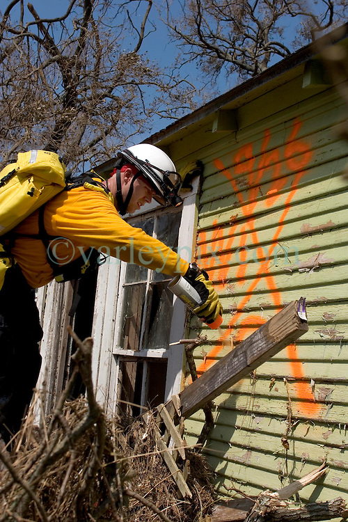 26th Sept, 2005. Hurricane Rita aftermath, Cameron, Louisiana. Members of the Las Vegas, Nevada Task Force 1, a FEMA search and rescue team scour the destroyed remains of houses and business in Cameron, Louisiana for any signs of life. A rescuer marks the outside of a house with spray paint to indicate no victims.