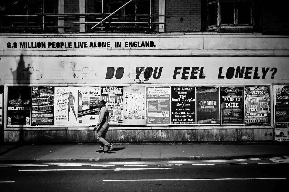 Liverpool, UK - 16 August 2012: A man walks by a graffiti at night reading '6.8 million people live alone, in England. do you feel lonely?'
