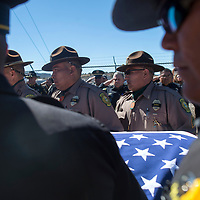 Navajo Nation Police Officers and McKinley County Sheriff Officers carry the casket of Navajo Nation Police Officer Houston Largo to his final resting place in Sunset Memorial Park in Gallup Thursday March 16 during his burial service.