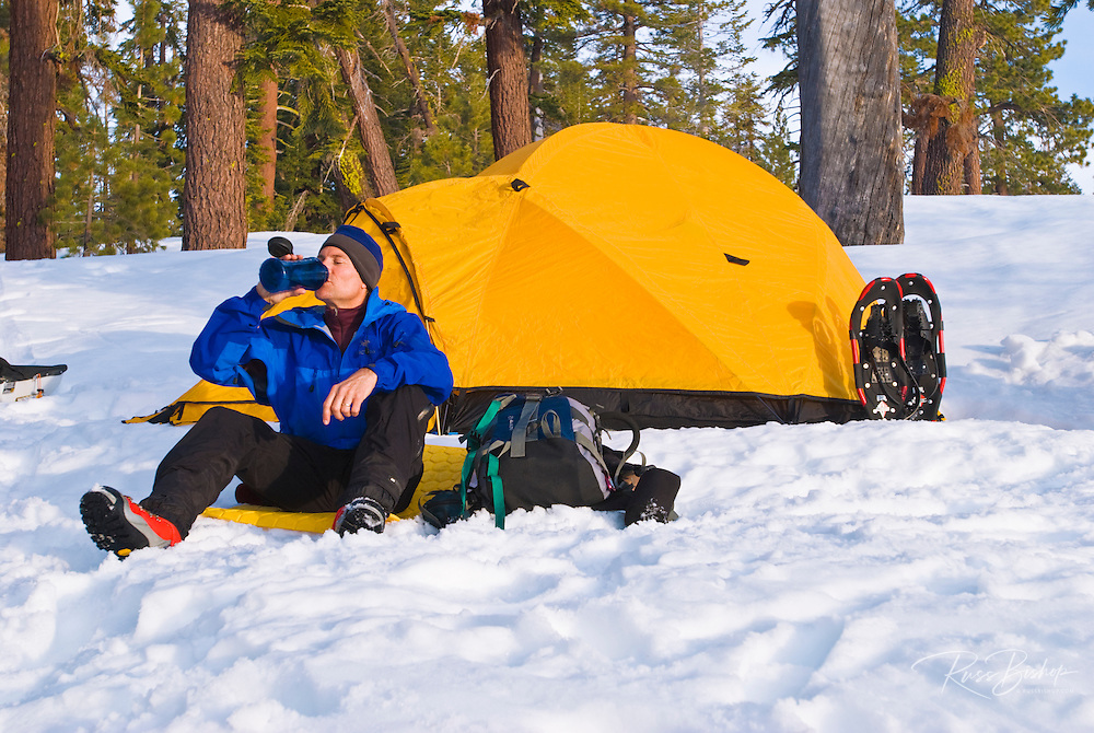 Backcountry skier (drinking from bottle) and yellow dome tent, Yosemite National Park, California