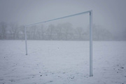 A football pitch and empty landscape of snowbound goal posts in wintry public park in south London. During a prolonged cold spell of bad weather, snow fell continuously on the capital on Sunday, allowing families the chance to enjoy the bleak conditions, here in Ruskin Park in the borough of Lambeth. The football goalpost, part of a soccer pitch used by local teams is otherwise unused as the weather forces local games to be cancelled before the grass beneath is again revealed. In the distance are Edwardian period houses beneath 100 year-old ash trees.