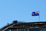 A New South Wales State Flag flying atop the arch of the Sydney Harbour Bridge. A group of tourists can be seen climbing the bridge, one raising his/her arms in triumph. Sydney, Australia