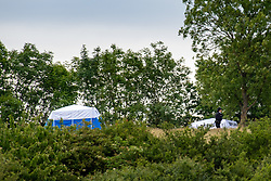 © Licensed to London News Pictures. 07/06/2020. London, UK. A Police officer walks past forensic tents sitting on the ridge of a hill in Fryent Country Park. The bodies of two women have been found in Fryent Country Park in Wembley. Metropolitan Police Service were called at 13:08 BST, Officers found two unresponsive woman, they were pronounced dead at the scene. Photo credit: Peter Manning/LNP