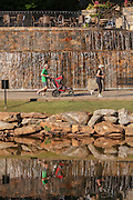 Runners at the Art Crossing and River Place development on the Reedy River in downtown Greenville, South Carolina.
