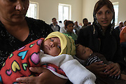 Two Roma infants and their mothers during a baby dedication ceremony in the Pentecostal church in the village of Valea Seaca in Bacau County, Romania.