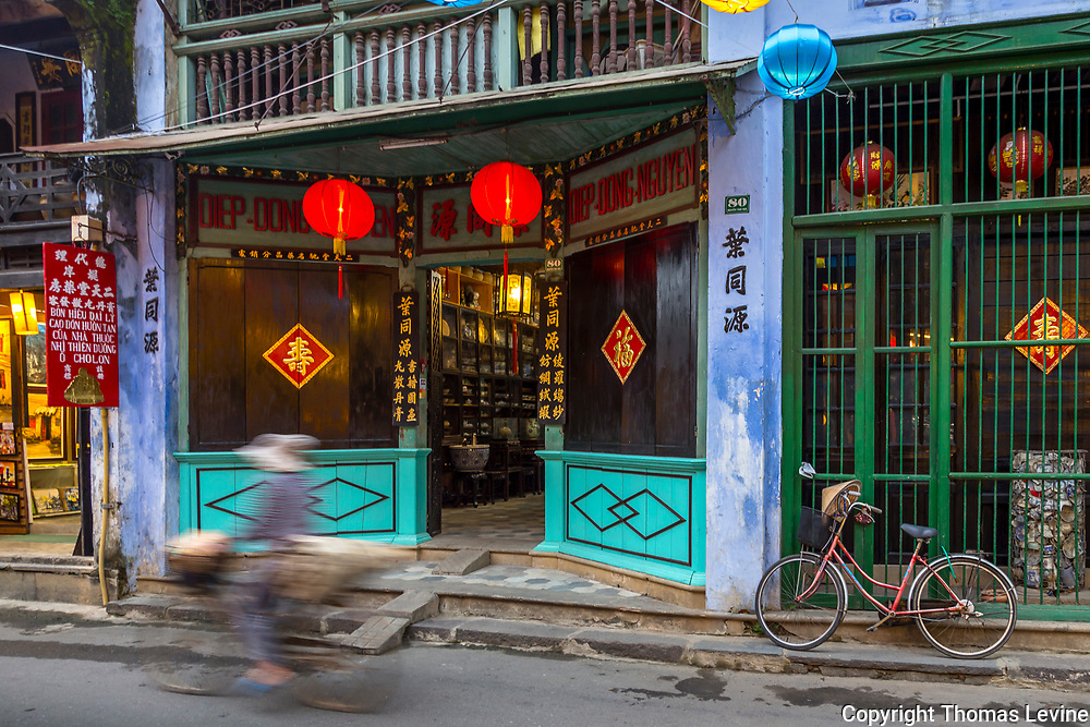 A rider in motion rides by store fronts in Hoi An with a parked bicyle.