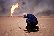 An unexploded rockeye submunition (cluster bomb), in the Manageesh Oil Field. After finding these rockeye submunitions all over Kuwait, the British Explosive Ordinance Disposal Team detonate them with plastic explosives from a safe distance. When they are found close to a burning oil well, a string is attached and it is dragged to a cooler distance to be detonated. Nearly a million land mines were deployed on the beaches and along the Saudi and Iraqi border. In addition, tens of thousands of unexploded bomblets (from cluster bombs dropped by Allied aircraft) littered the desert. July 1991. More than 700 wells were set ablaze by retreating Iraqi troops creating the largest man-made environmental disaster in history.