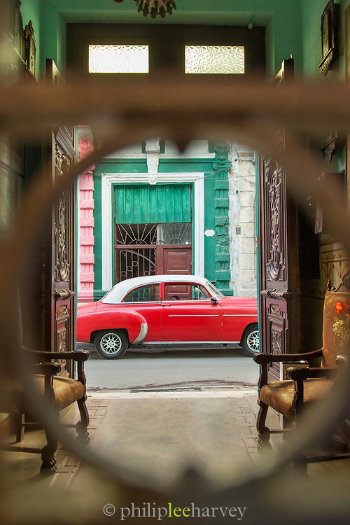 View for street San Cristobal Paladar with vintage car from behind bars, Havana, Cuba