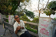 An old man sits on a bench on the Strand overlooking the Hoogley River, Chandannagar, India