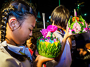 "03 NOVEMBER 2017 - BANGKOK, THAILAND: Girls pray before floating their krathong during Loi Krathong at Wat Prayurawongsawat on the Thonburi side of the Chao Phraya River. Loi Krathong is translated as ""to float (Loi) a basket (Krathong)"", and comes from the tradition of making krathong or buoyant, decorated baskets, which are then floated on a river to make merit. On the night of the full moon of the 12th lunar month (usually November), Thais launch their krathong on a river, canal or a pond, making a wish as they do so. Loi Krathong is also celebrated in other Theravada Buddhist countries like Myanmar, where it is called the Tazaungdaing Festival, and Cambodia, where it is called Bon Om Tuk.     PHOTO BY JACK KURTZ"