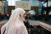 Veiled Londoner inside during the opening day of the Westfield Stratford shopping mall. Situated on the fringe of the 2012 Olympic park, Westfield hosted its first day to thousands of shoppers eager to see Europe's largest urban shopping centre. The £1.45bn complex houses more than 300 shops, 70 restaurants, a 14-screen cinema, three hotels, a bowling alley and the UK's largest casino. It will provide the main access to the Olympic park for the 2012 Games and a central 'street' will give 75% of Olympic visitors access to the main stadium so retail space and so far 95% of the centre has been let. It is claimed that up to 8,500 permanent jobs will be created by the retail sector.